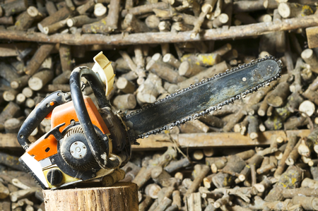 firewood background: professional chainsaw  in stump with unfocused  firewood background Stock Photo