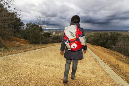 camino de santiago: pilgrim woman walking in Way of St James, Camino de Santiago, to Compostela, Astorga, Spain Stock Photo