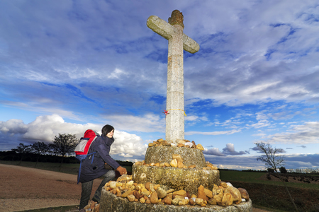saint jacques: woman pilgrim placed pebbles  with messages on the cross  in Way of St James,  Camino de  Santiago, to Compostela, Astorga , Spain