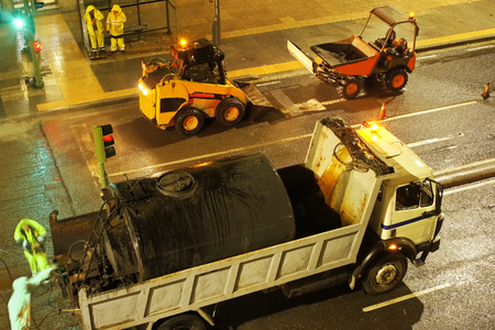 skid steer loader: for construction workers repairing the crosswalk in the city road with skid steer loader vehicle at night