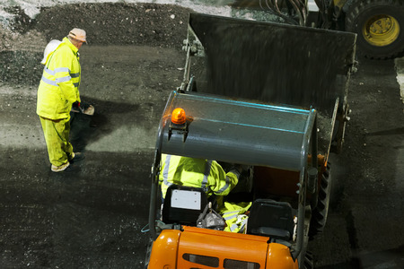 skid steer: for construction workers repairing the crosswalk in the city road with skid steer loader vehicle at night