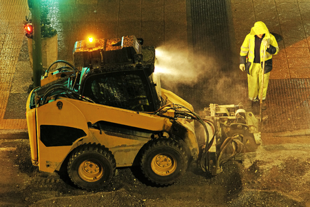 augers: for construction workers repairing the crosswalk in the city road with skid steer loader vehicle at night