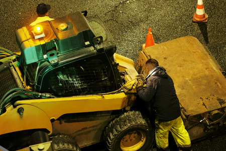 augers: construction workers for repairing  the crosswalk in the city road with skid steer loader vehicle at night Stock Photo