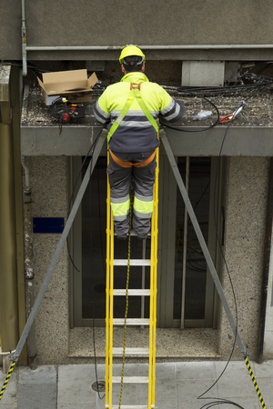 protective equipment: professional worker with safety protective equipment  to install internet , tv and phone with optical fiber system in the building facade