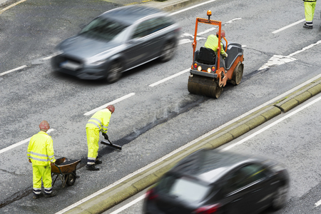 resurfacing: maintenance  workers for covering  potholes for repair the highway in  city Stock Photo