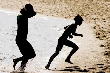 swim race: triathletes silhouettes  on the shore beach after swim race portion
