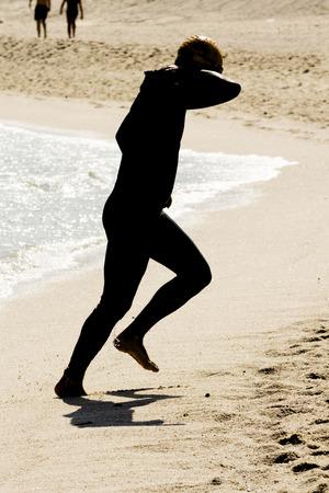 swim race: triathlete shore silhouette on the beach after swim race portion