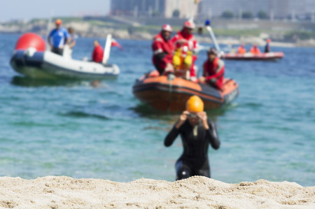 swim race: triathlete and rescue boats unfocused with focused sand on the shore beach after swim race portion