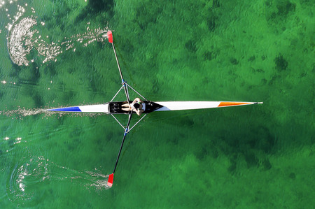 sculling: rower in scull , skiff, in  the  sea in aerial view Stock Photo