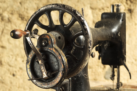 machine made: vintage  manual sewing machine made of metal with painted design in old  mud  house