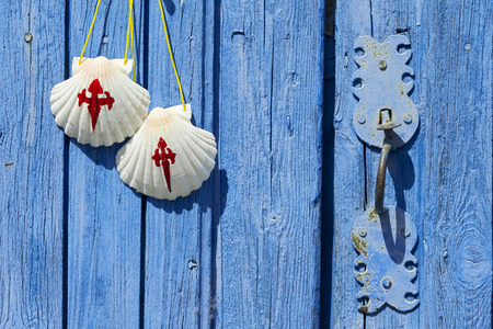 way of st  james: pilgrim scallops on antique wooden door , Way of St James,  Camino de  Santiago, to Compostela,Villarejo de Orbigo village, Leon, Spain