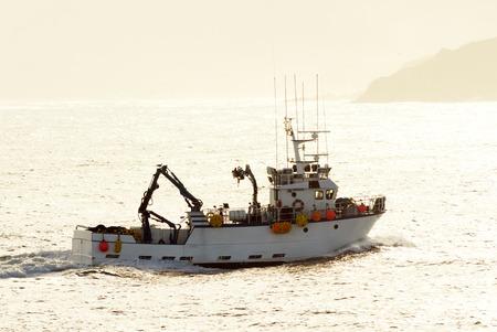 navigating: professional fishing  boat in  navigating at sunrise in atlantic coast Stock Photo