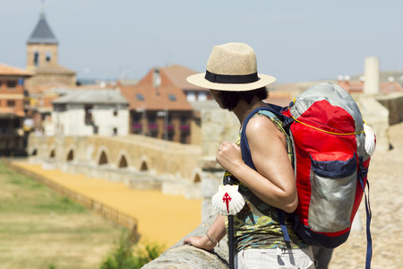 st jamess: pilgrim in the Hospital de Orbigo bridge, Way of St James, Camino de Santiago, to Compostela, Leon, Spain