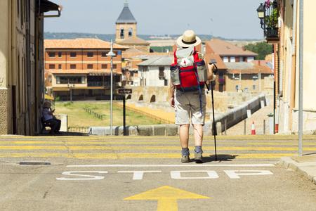 way of st  james: yellow arrow sign with pilgrim in Hospital de Orbigo bridge, Way of St James, Camino de Santiago, to Compostela, Leon, Spain