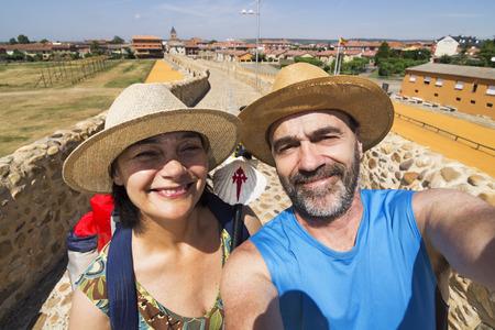way of st  james: couple pilgrims selfie in Hospital de Orbigo bridge  , Way of St James,  Camino de  Santiago, to Compostela, Leon, Spain