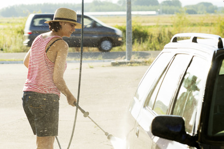 woman washing your car  with  with high pressure water jet at service station