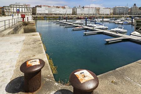 bollards: bollards in marina port of Coruna, Spain, with sailboats, yachts and fishing boats moored professional