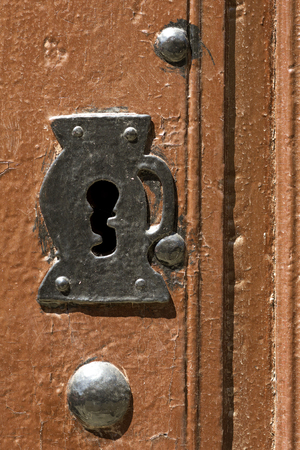 old wooden door with locks and handle of rusty iron , background