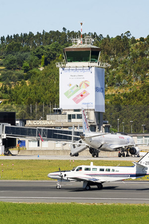 Coruna, Spain - August 2 2016: air traffic control tower of Alvedro With Air Europa plane on the terminal and aircraft on runway, Coruna, Spain