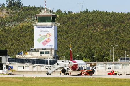 Coruna, Spain - August 2, 2016: air traffic control tower of Alvedro With Iberia plane on the terminal, Coruna, Spain