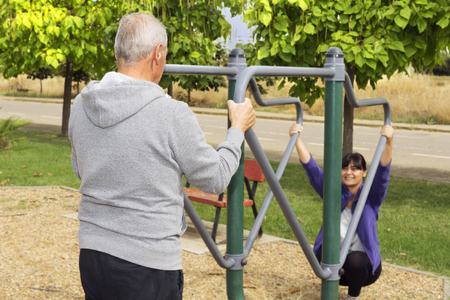 exercice: woman and elderly man Exercising with fitness equipment in public outdoor gym, selective focus on man