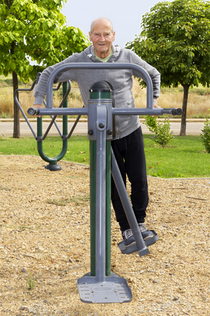 exercice: old man  training  with  fitness equipment in public outdoor gym