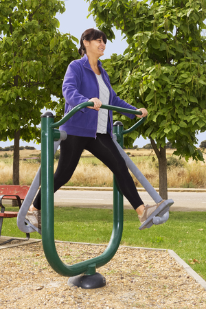 exercice: woman training with  fitness equipment in public outdoor gym Stock Photo