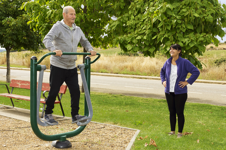 exercice: woman and elderly man exercising with  fitness equipment in public outdoor gym Stock Photo