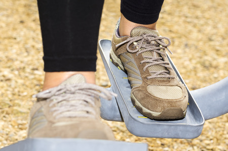 exercice: woman feet  in training  with  fitness equipment in public outdoor gym , selective focus