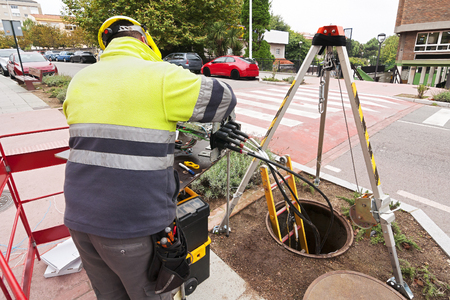 adsl: worker electrician install optical fiber system in city street Description: electrician install optical fiber system worker in city street