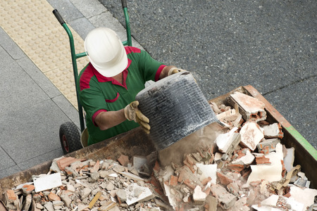 depositing: bricklayer mason worker depositing waste of bricks and tiles in rubble dumpster container in street city Stock Photo