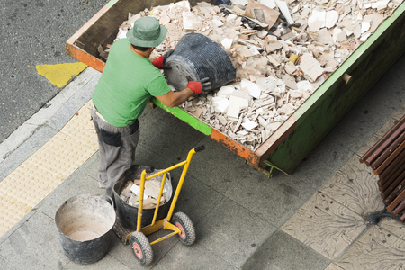 depositing: bricklayer mason worker depositing waste of bricks and tiles in rubble container in street city