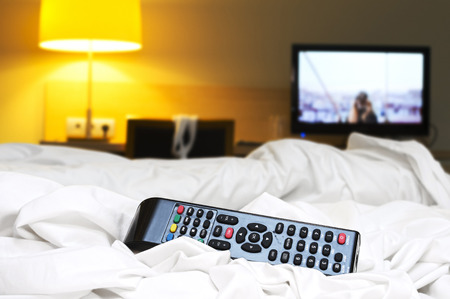 communicable: remote tv control on hotel bed  dangerous  for infection by bacteria Stock Photo