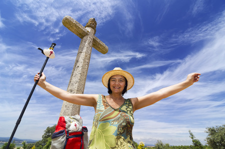 pilgrim with stone cross  near Astorga , Way of St James,  Camino de  Santiago, to Compostela, Leon, Spain