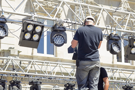 professional lighting: lighting technician intstalling professional  lighting equipment for concert stage , installation with led lights and projectors