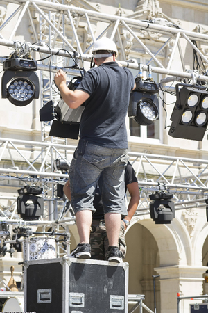 led lighting: lighting technician intstalling professional  lighting equipment for concert stage , installation with led lights and projectors