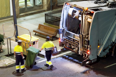 recolector de basura: garbage collector truck vehicle with municipality workers  in  street  city at night Foto de archivo