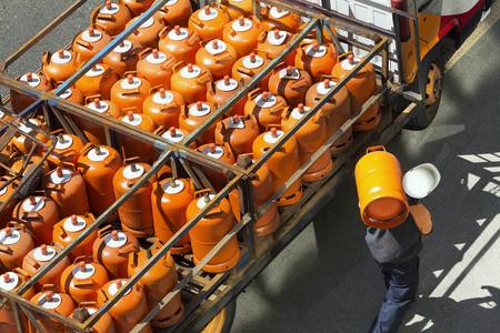 butane: gas bottles with butane in truck with  worker for delivery Stock Photo