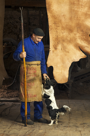 tannins: tanner  with old tools and machinery  in the antique mud tannery  Stock Photo