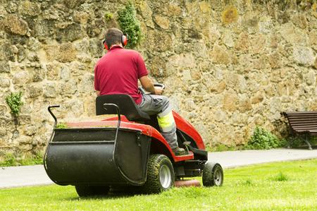 grass cutting: mower lawnmower  and gardener cutting the grass Stock Photo