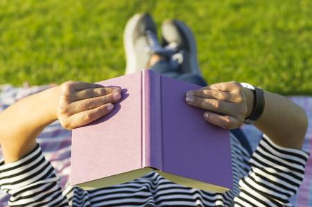 handkerchief: Woman reading book on grass, close up