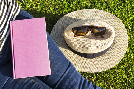 hankie: Woman with book and hat on grass Stock Photo