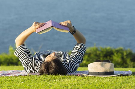 Woman reading book near sea Stock Photo