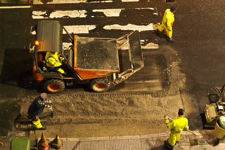 asphalting: construction workers for repairing  the crosswalk in the city road with skid steer loader vehicle at nigth