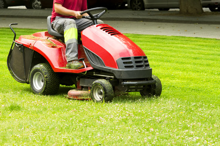 mower lawnmower  and gardener cutting the grass Stock Photo