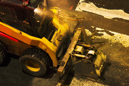 skid steer loader: construction workers for repairing  the crosswalk in the city road with skid steer loader vehicle at nigth