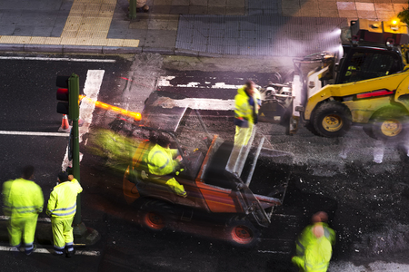 construction workers for repairing  the crosswalk in the city road with skid steer loader vehicle at nigth
