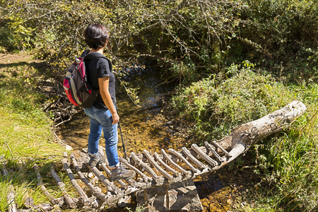 slog: trekking and hiking, woman in wooden bridge over river