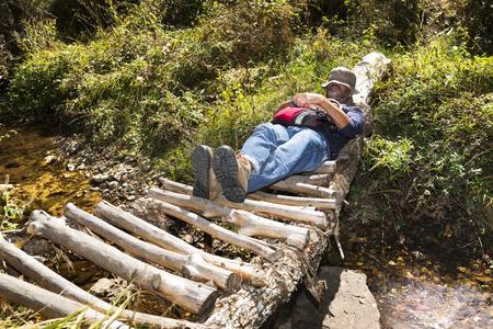 slog: trekking and hiking, man in wooden bridge over river