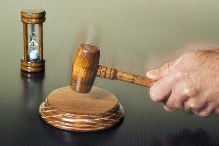 Auction bid sale judgment mallet with judge auctioneer hand and hourglass unfocused